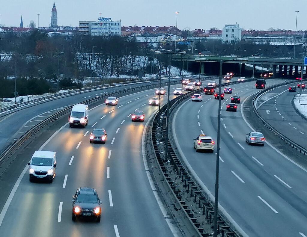 Blick von der Autobahnbrücke, auf die Autobahn. Abendliche Stimmung, die Scheinwerfer sind eingeschaltet