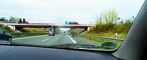 Autobahn, Seitenstreifen. Rechts Warndreieck, weiter hinten Pannenfahrzeug